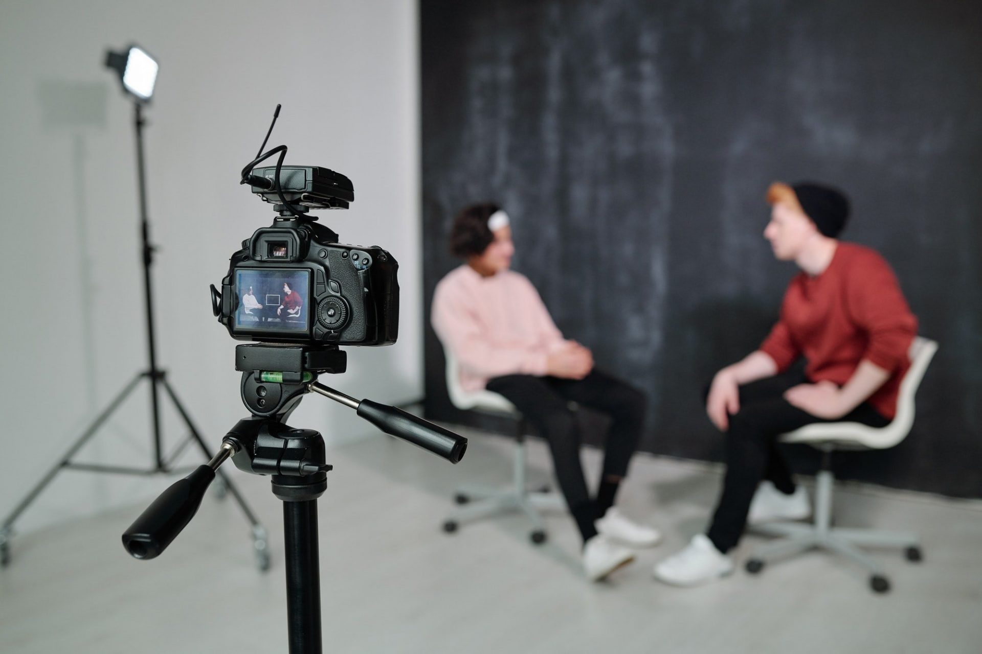 Screen of digital video camera with two vloggers having conversation in studio
