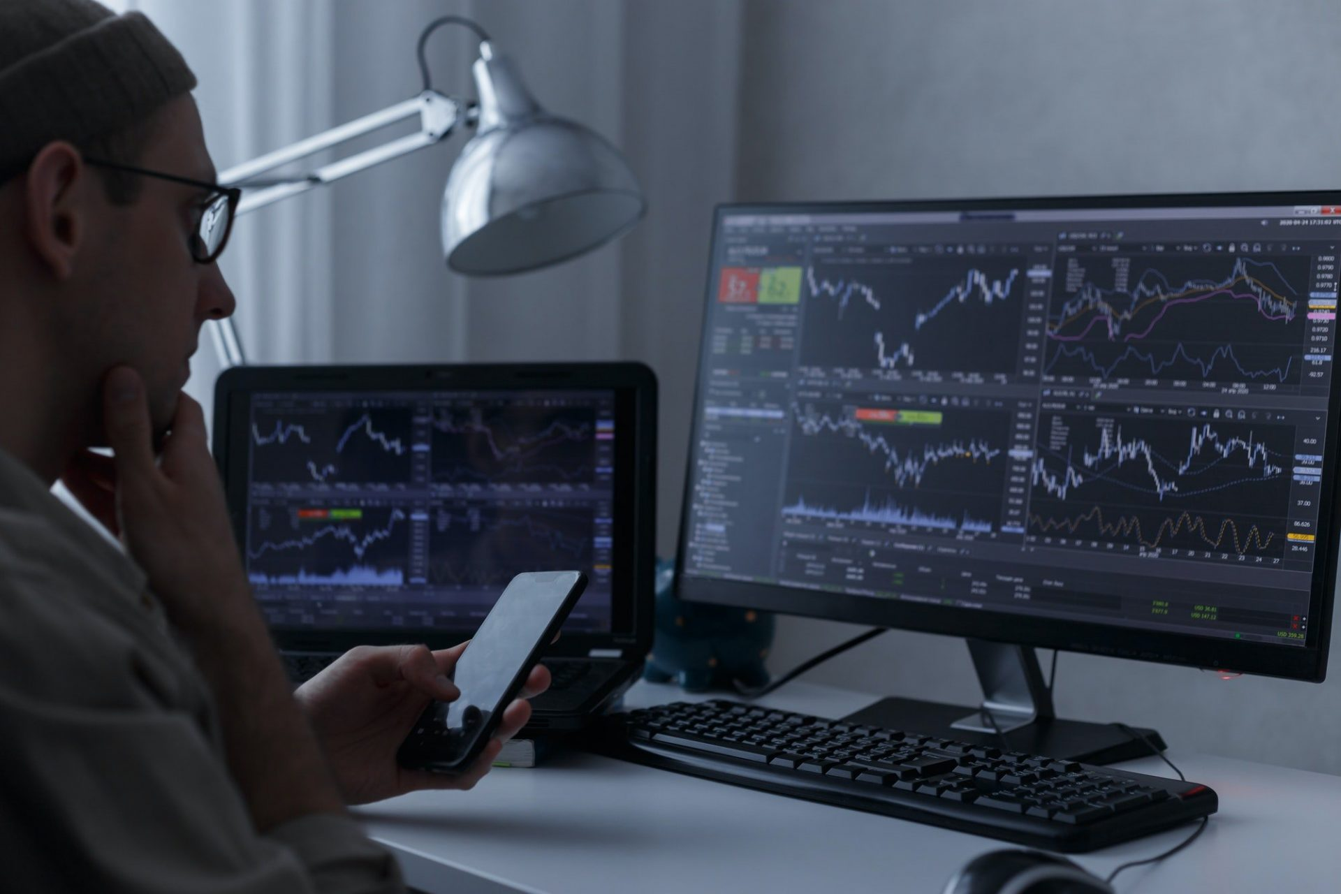 Trader analysing financial graph and stock statistics on monitors at his home workplace